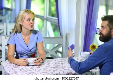 Girl with blond hair and bearded guy on light cafe background. Couple in love holds cups of coffee at table. Woman with busy face and man have a date. Rendezvous and coffee break concept