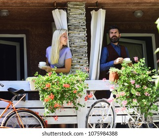 Girl with blond hair and bearded guy on cafe background. Rendezvous and coffee break concept. Couple in love holds cups of coffee. Woman and man with smiling faces have a date on terrace with bikes
