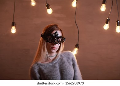 A girl with blond hair in a black mask poses
