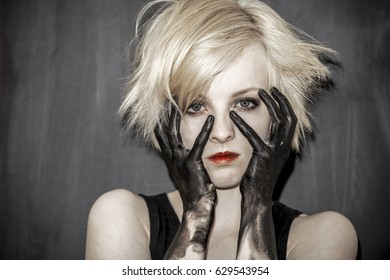 Girl with blond hair and black painted hands