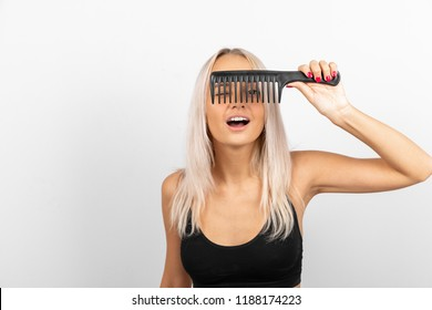A girl with blond hair in a black T-shirt holds a black plastic comb in her hand and looks through a comb on a white background