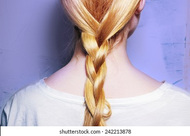 Girl with blond hair, braided into a braid on a purple background