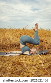 girl with blond hair in a tracksuit practices yoga in a wheat field