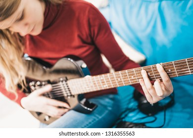 Girl with blond long hair plays hard rock on a black electric guitar