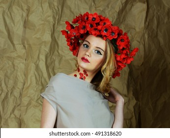 Girl blonde in a beige dress with lace. At the head of the girl wreath of poppies. On the neck and hand painted poppies.