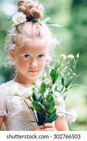 the girl the blonde with blue eyes in the summer outdoors with flowers