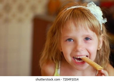 Girl blonde eats sweet wand and smiles. She is happy