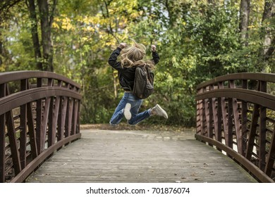 Girl with blonde hair jumping on a bridge wearing a backpack.