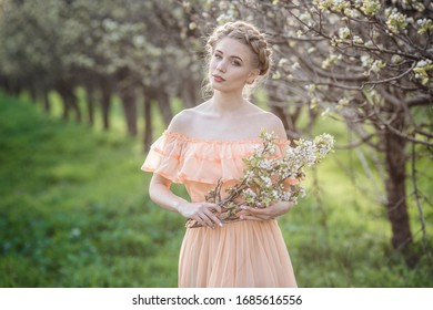 girl with blonde hair in a light dress in flowering garden. concept of female spring fashion. Young model looking at camera expressive.
