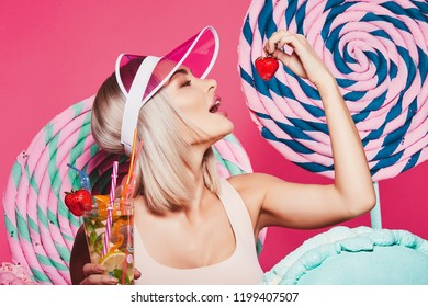 Girl with blonde hair wearing top and pink cap standing with huge sweet lollypops at pink background, candy lover, drinking lemonade, eating strawberry.