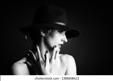 Girl blonde in a hat. Black and white photo. Studio photography.