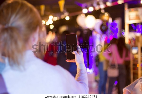 the girl the blonde holds the phone in hand and photographs. dark screen of phone. a photo from a back.