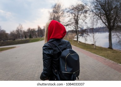 girl, blonde, in a leather jacket walks on a summer park in the street