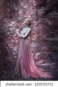 Girl blonde in a luxurious pink dress. The sorceress holds magic in her hands. Elven hairstyle, creative braid. Background fairy forest. Unusual, artistic photo processing.