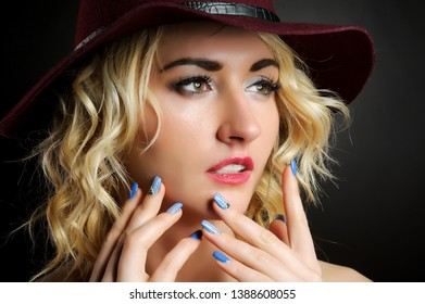 Girl blonde in a red hat. Studio photography.