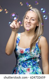 girl blonde with soap bubbles on white background