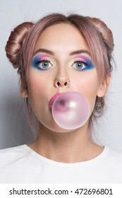 Girl blowing big bubble gum. Beauty fashion model girl with two pink bun hairstyle and colourful make-up isolated on white background
