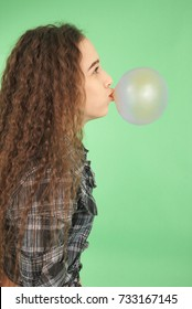 Girl blowing a bubblegum bubble isolated on green