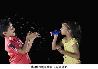 Girl blowing bubbles and a boy looking at his palm