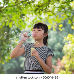 The girl is blowing bubbles in the park