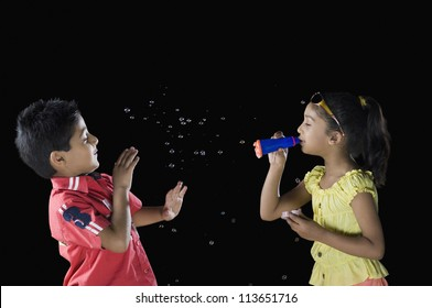Girl blowing bubbles towards a boy