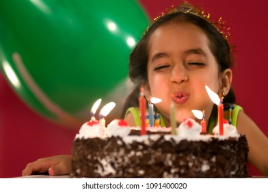 A girl blowing the candles