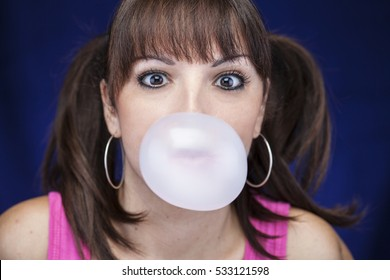 Girl blowing chewing gum bubble balloon