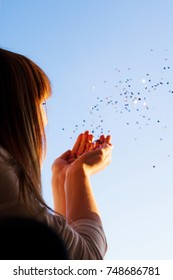 A girl blowing glitters into the sky