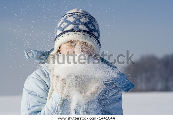 Girl blowing into snow