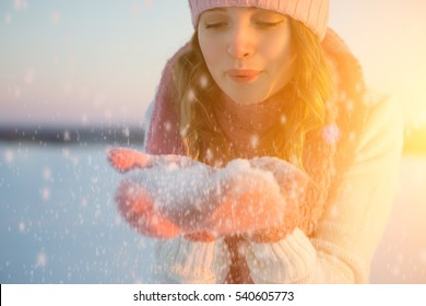 Girl blowing on the snow in the park in winter. Beauty girl in hat and scarf.
