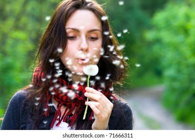 Girl blowing on white dandelion in the forest