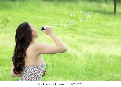 girl blowing soap bubbles on a green grass background