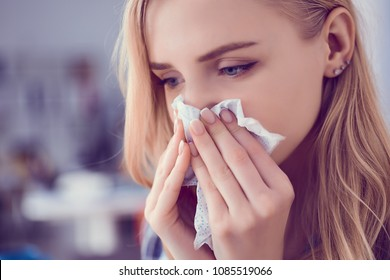 Girl blows her nose into a tissue. Portrait of a woman with tissue in hands looking away. Concept of treatment for allergies or the common cold.