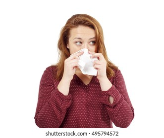 girl blows her nose into a tissue. portrait of a woman with tissue in hands. looking away. the concept of treatment for allergies or the common cold. isolated on white background