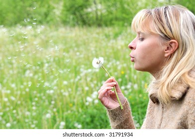 Girl blows on dandelion and thinks desire