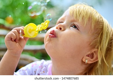 Girl blows soap bubbles for game design. Colorful background. Positive person. Healthy hair. Bubbles blowing. Summer leisure. photo