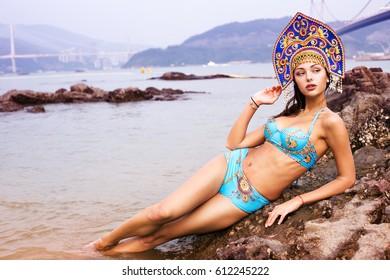 A girl in a blue bikini and with a Russian kokoshnik on her head lies on the beach