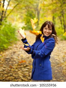 Girl in blue coat throwing leaves in the air