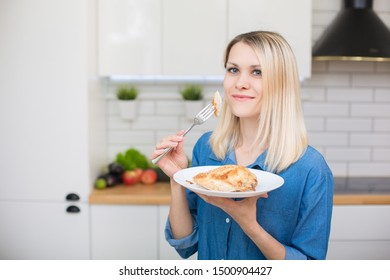 A girl in a blue denim shirt is holding a plate with ready-made chicken breast white meat. Dietary and proper nutrition