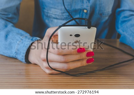 The girl in the blue denim shirt sitting at the table and listens to music on a white phone. In the foreground can be seen a wooden table. The phone in her right hand with red manicure. Vintage photo.