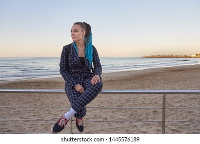 A girl with blue dreadlocks and a plaid suit sits on an iron railing against the beach and the sea.