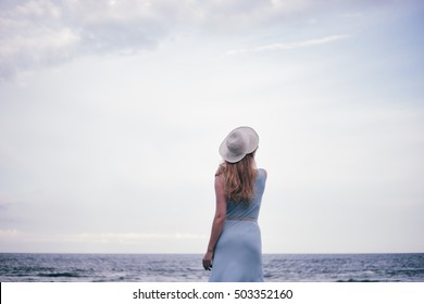 girl in a blue dress and hat walking on the sea, hair developing on wind