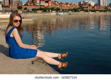 girl in a blue dress on the background of the river. Ukraine. Kiev. Obolon