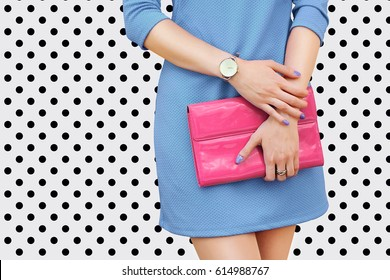 Girl in blue dress with pink bag clutch. Fashion concept. White black polka dots background.