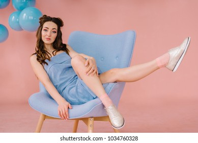 a girl in a blue dress in a pink room is lying on a blue armchair and smiling, lifting her arms up. From the ceiling hang blue balls