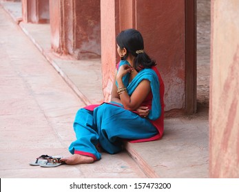girl in blue dress siting in a temple