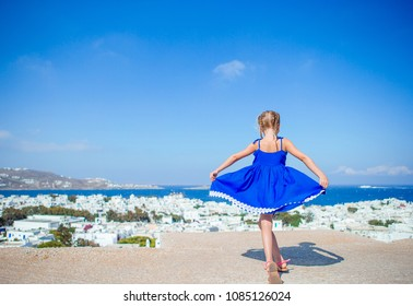 Girl in blue dresses having fun outdoors with amazing view of Mykonos