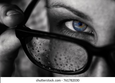 A girl with blue eyes looks over her glasses. Glasses covered with drops of water (rain). Image black and white with a emphasis on the eye.