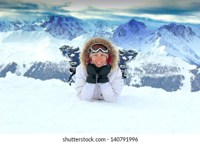 Girl with blue eyes is lying on the snow in mountains