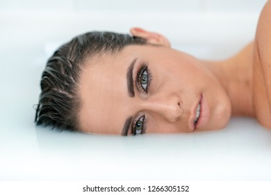 Girl with blue eyes and wet hair inside a bath of milk
